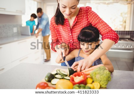 Close-up of happy mother teaching daughter to cut vegetables at home - stock photo