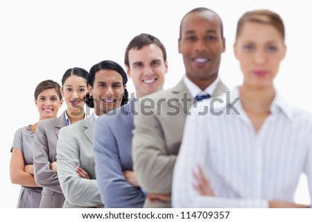 Close-up of happy workmates dressed in suits crossing their arms in a single line with focus on the last two people - stock photo