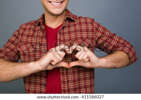 Close up of  happy young man making heart with fingers - stock photo
