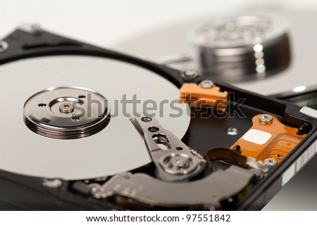 close up of hard disk with blurred another hard disk in background - stock photo