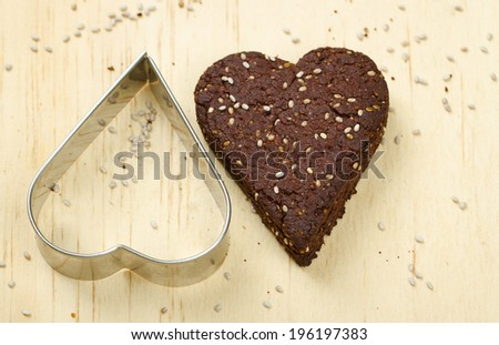 Close-up of healthy dark chocolate and chia seed cookies on wooden background with cookie cutter - stock photo