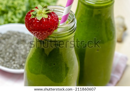 Close up of healthy green juice smoothie in glass bottle sitting on yellow napkin with fresh strawberries and kale - stock photo