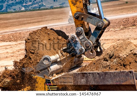 close-up of heavy duty excavator scoop loading a dumper truck with earth from construction site - stock photo
