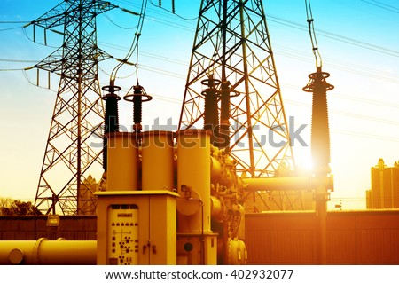 Close-up of high-voltage power substation equipment, evening landscape. - stock photo