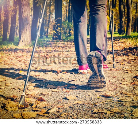 Close up of hinking woman feet and nordic walking poles. Vintage retro effect filtered hipster style image - stock photo