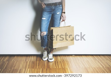 Close-up of hipster girl wearing blue jeans and holding blank craft paper package, mock-up of template brown shopping bag with handles - stock photo