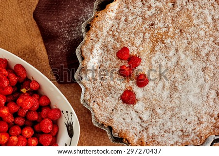 Close-up of homemade cakes, charlotte with berries sprinkled with sugar on top, in the frame you can see the white dishes with dark colors which is a strawberry - stock photo