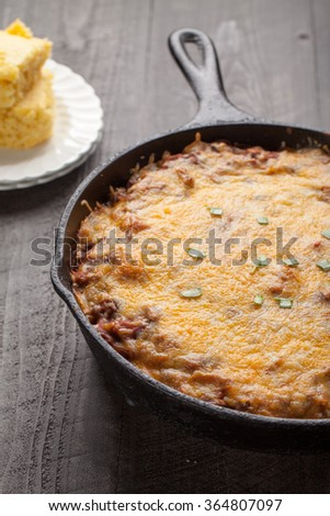 Close up of homemade chili baked in cast iron skillet with side of cornbread - stock photo