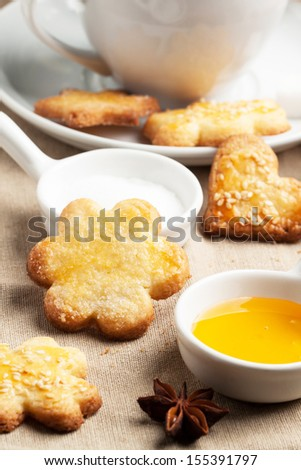 Close up of homemade sugar cookies with honey and anise over textile - stock photo