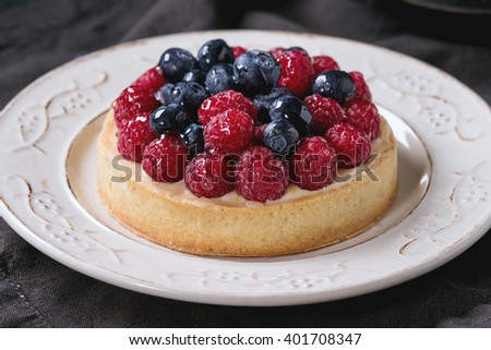 Close up of Homemade tart with custard, fresh raspberries and blueberries, served on white vintage plate on textile napkin over old wooden table. Dark rustic style - stock photo
