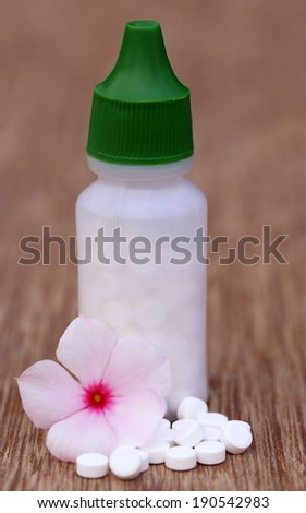 Close up of Homeopathic medicine with herbal flower - stock photo