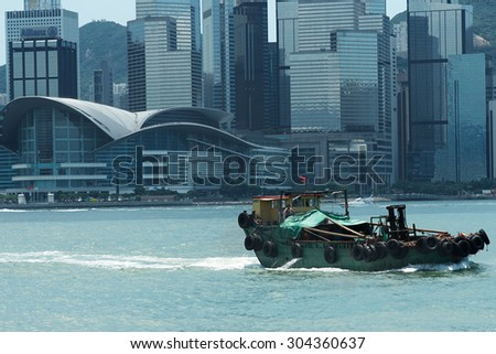 Close -up  of Hong  Kong - tradition and modernity. Old boat on the background of modern business buildings in Hong Kong. - stock photo