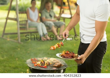 Close-up of host serving delicious grilled meal - stock photo