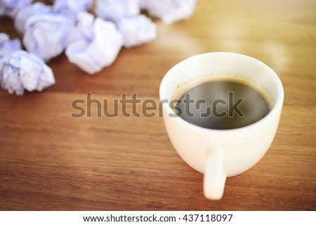 Close up of hot coffee with crumpled paper background, selective focus on coffee, vintage style. Business concept in finding idea. - stock photo