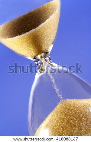 Close up of hourglass on blue background - stock photo
