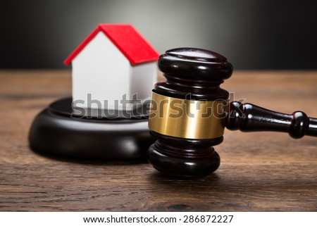 Close-up Of House Model With Gavel On Wooden Table - stock photo