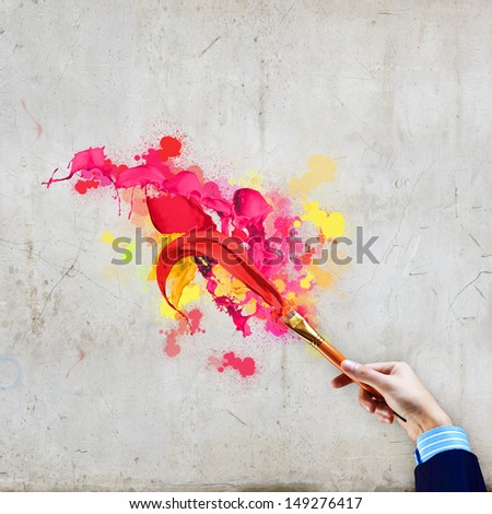 Close-up of human hand holding paint brush making colorful paint splashes - stock photo