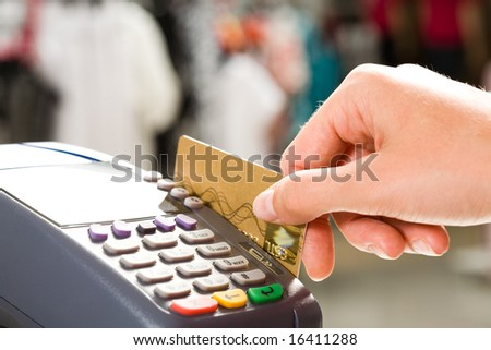 Close-up of human hand holding plastic card in payment machine - stock photo