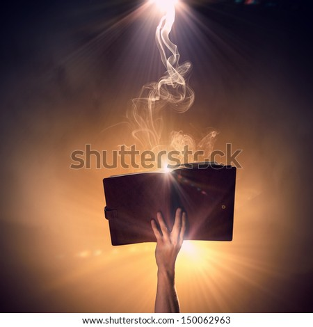 Close up of human hand holding saint book - stock photo