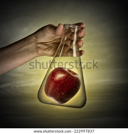 Close up of human hand holding test tube with apple - stock photo