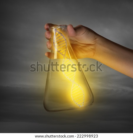 Close up of human hand holding test tube with dna - stock photo