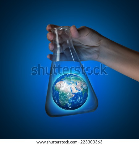 Close up of human hand holding test tube with Earth planet. Elements of this image are furnished by NASA - stock photo