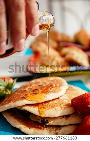 Close Up Of Human Hand Overflowing Maple Syrup On Pancakes With Raisins And Strawberries Around - stock photo