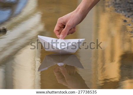Close-up of human hand putting paper ship lying onto still water - stock photo