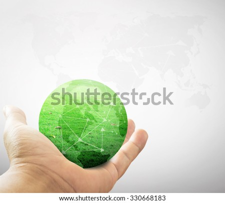 Close up of human hand showing a green earth of grass over blurred world map of clouds background. World Environment Day. Ecological city concept. - stock photo
