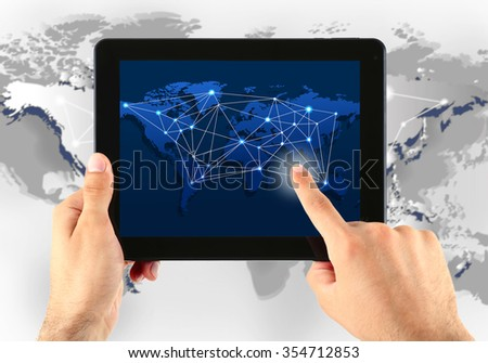 Close up of human hand touching screen of tablet pc with world map and network - stock photo