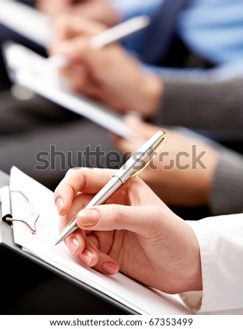 Close-up of human hand with pen writing something - stock photo