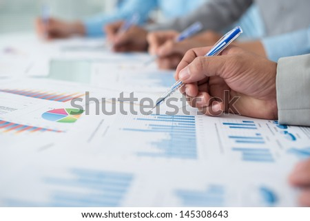 Close-up of human hands analyzing the business diagrams on the foreground - stock photo