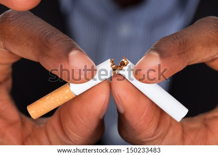 Close-up Of Human Hands Breaking The Cigarette - stock photo
