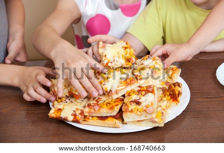 Close-up of human hands cutting pizza - stock photo