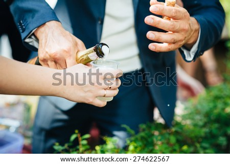Close-up of human hands holding glasses of champagne. - stock photo