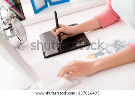Close-up of human hands retouching photos using digital tablet on the foreground - stock photo