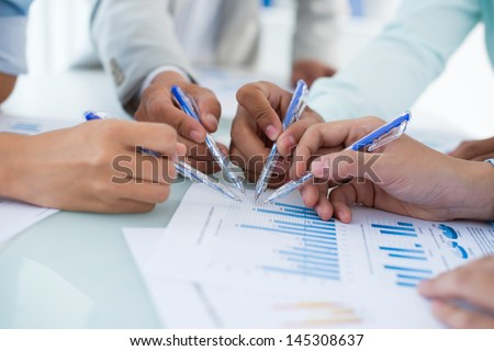 Close-up of human hands with ballpoints pointing at the graphs - stock photo