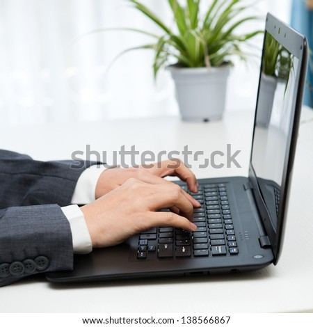 Close-up of human hands working on laptop. - stock photo