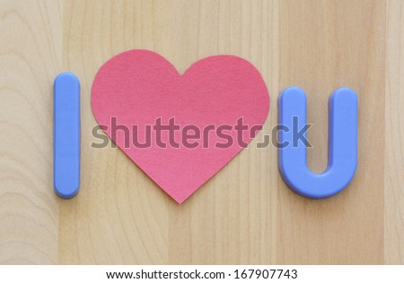 Close up of I love U in plastic blue letter toys and pink heart shape cut out paper on natural wooden background - stock photo