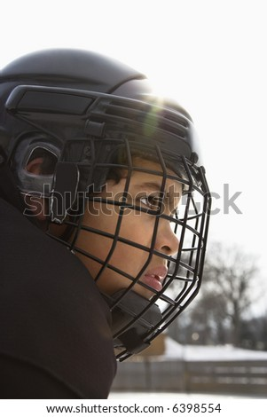 Close up of ice hockey player boy in cage helmet with look of concentration. - stock photo