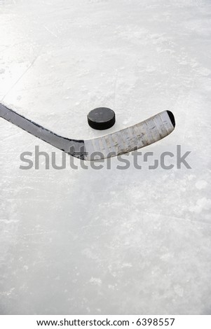 Close up of ice hockey stick on ice rink in position to hit hockey puck. - stock photo