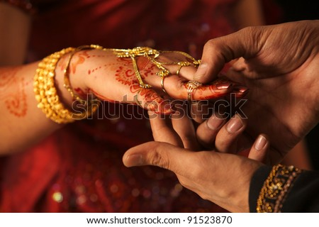 Close up of Indian couple's hands at a wedding, concept of marriage/partnership/commitment - stock photo
