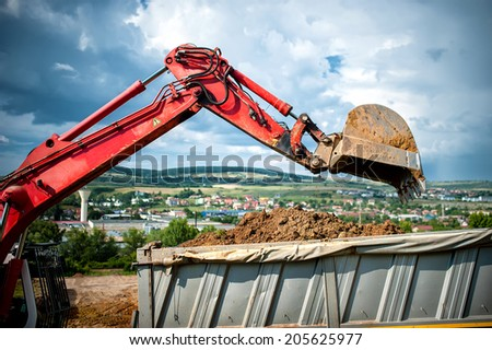 close-up of industrial excavator loading a dumper truck with soil and earth from construction site - stock photo