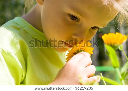 Close-up of innocent girl enjoying nice smell of flowers outdoors - stock photo