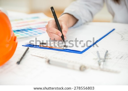 Close-up of interior designer working with architectural plan in her modern home office. - stock photo