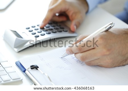 Close-up of investment advisor calculating expenses while sitting at office in front of computer. - stock photo