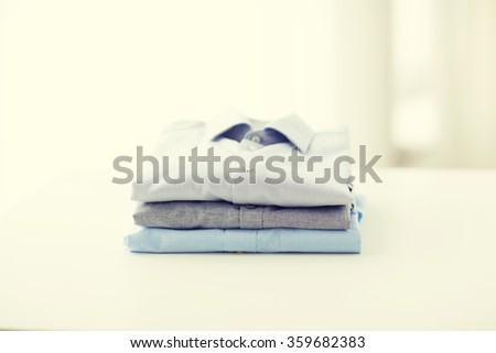 close up of ironed and folded shirts on table - stock photo