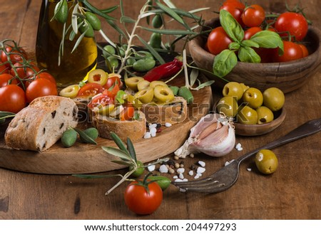 Close up of italian tomato bruschetta with chopped olives, garlic, herbs and olive oil on  ciabatta bread on the wooden table - stock photo