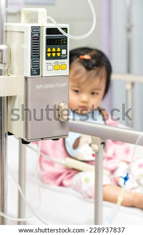Close-up of IV machine with the child in the background - stock photo