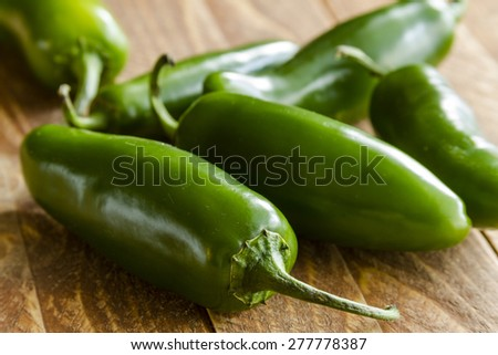 Close up of jalapeno peppers sitting on wooden table - stock photo